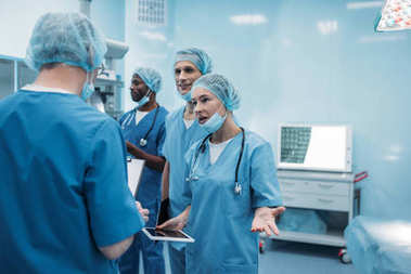 four multiethnic surgeons talking in operating room