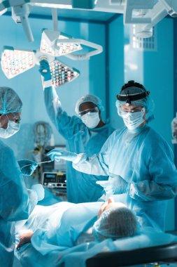 multiethnic surgeons operating female patient