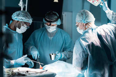 multiethnic surgeons in medical masks operating patient in operating room