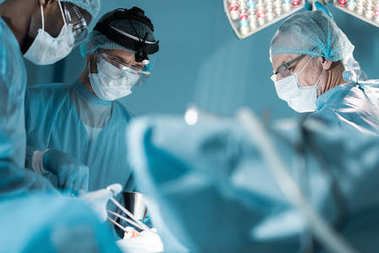multicultural surgeons in medical masks operating patient in operating room