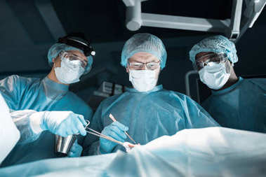 multicultural surgeons operating patient in operating room