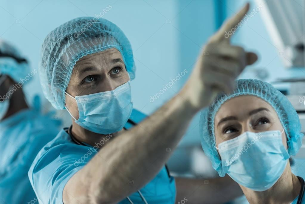 doctor pointing on something in surgery room