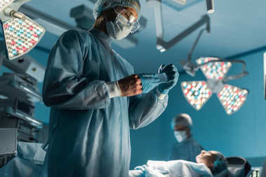 surgeon taking off medical gloves near patient in surgery room