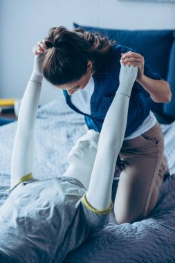 woman playing with mannequin on bed at home, one way love concept
