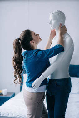 side view of cheerful young woman hugging mannequin, perfect relationship dream concept