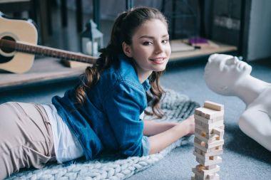 """Картина, постер, плакат, фотообои """"красивая женщина, лежа возле манекена и блоков древесины игра на этаже дома, концепция одиночество"""", артикул 184008684"""