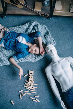 overhead view of woman and mannequin lying on floor near blocks wood game, perfect relationship dream concept