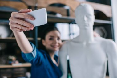 selective focus of smiling woman taking selfie together with mannequin, perfect relationship dream concept