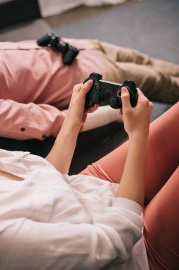 cropped shot of woman with manikin near by playing video game at home, loneliness concept