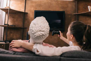 back view of woman with manikin near by playing video game at home, loneliness concept