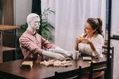 mladá žena hrát hru společně laik panenku u stolu s šálky kávy, samota koncepce