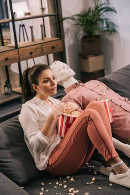 woman eating popcorn while watching film together with manikin at home, perfect relationship dream concept
