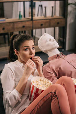 scared woman eating popcorn while watching film together with manikin at home, perfect relationship dream concept