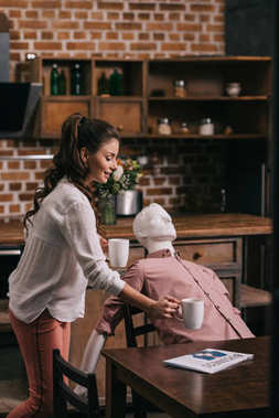 woman serving coffee to manikin at home, perfect relationship dream concept