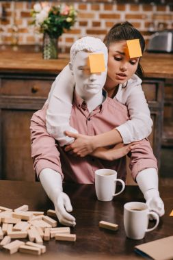 portrait of young woman with sticky note on forehead hugging layman doll, perfect relationship dream concept