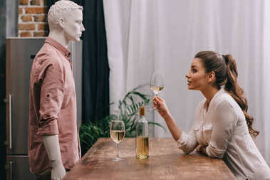 side view of young woman with glass of wine at table with male manikin, unrequited love concept