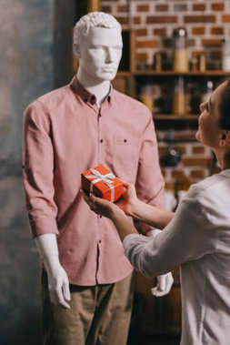 partial view of woman pretending to except gift from mannikin, loneliness and perfect man dream concept