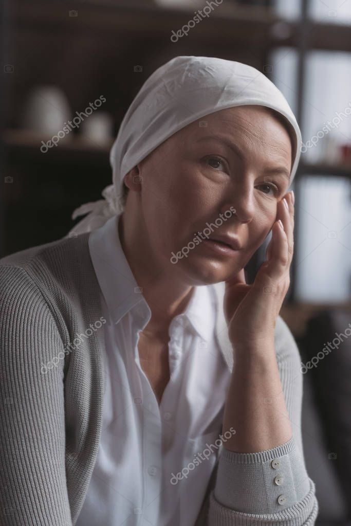 portrait of sick mature woman in kerchief looking at camera