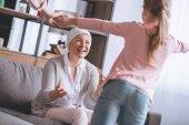 Fotografie Happy nemocné babičce v šátek na roztomilá malá vnučka