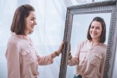 Fotografie beautiful smiling young woman standing near mirror and looking at reflection
