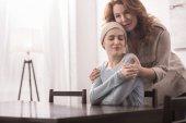 Fotografia donna matura che abbraccia e sostiene figlia malata sorridente in kerchief