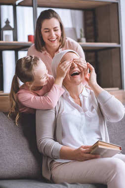 happy mother and daughter visiting sick smiling grandmother in kerchief reading book at home