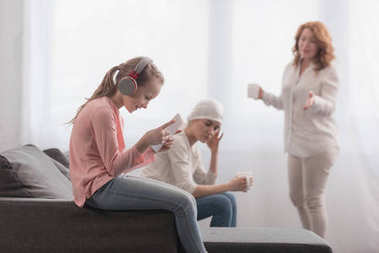 child in headphones using digital tablet while sick mother and grandmother talking behind