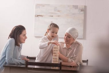 happy family of three generations playing with wooden blocks together, cancer concept