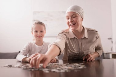 smiling kid with sick grandmother in kerchief playing with jigsaw puzzle together