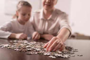 close-up view of grandmother and granddaughter playing with jigsaw puzzle together, cancer concept