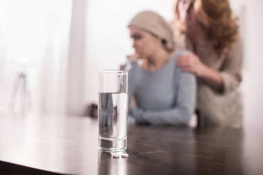 close-up view of glass of water and woman supporting sick daughter in kerchief behind