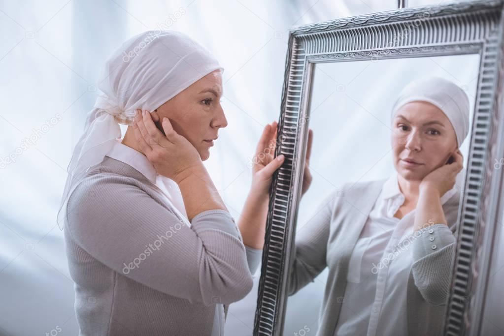 Serious sick mature woman in kerchief looking at mirror, cancer concept stock vector