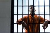 Fotografia prigioniero di mettere le mani tra le sbarre di una prigione