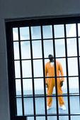 Fotografia afroamericano prigioniero dietro le sbarre di una prigione