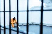 Fotografia prigioniero afroamericano che si siede sulla panchina dietro le sbarre della prigione