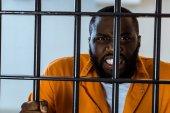 Fotografia arrabbiato prigioniero afroamericano che tiene sbarre di una prigione
