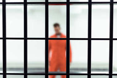 prisoner in prison cell with metallic bars on foreground