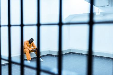 african american prisoner sitting on bench behind prison bars