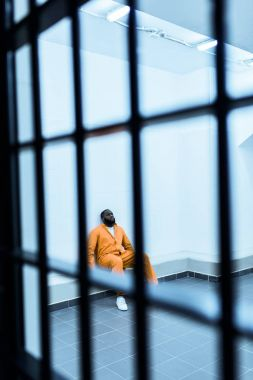 african american prisoner sitting on bench in prison cell