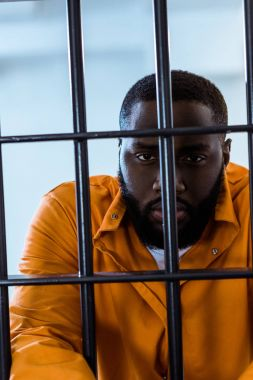 african american inmate looking at camera behind prison bars