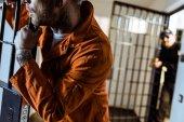 Oříznout obrázek vězně, opíraje se o mříže