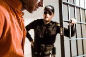 oříznutého obrazu vězeňské stráže při pohledu na zločince ve vězeňské cele