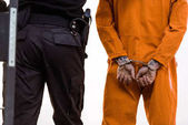 Photo cropped image of prison guard leading criminal in handcuffs