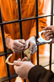 Photo cropped image of prison warden wearing handcuffs on prisoner