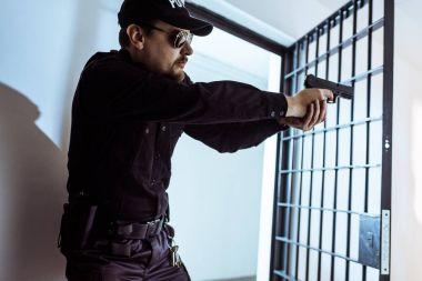 Prison guard aiming gun and looking away stock vector