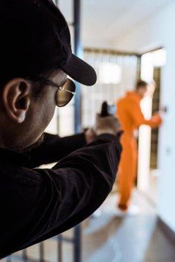 prison guard aiming gun at prisoner