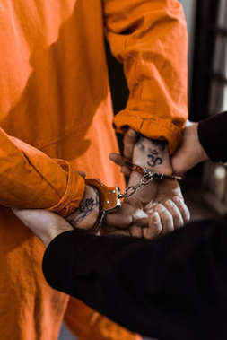 cropped image of prison officer holding convict in handcuffs