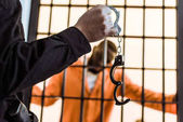 Photo cropped image of prison guard showing handcuffs to african american prisoner