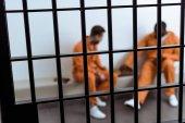 Fotografia multiculturali prigionieri giocano a scacchi dietro le sbarre della prigione