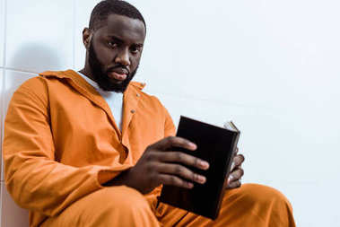 african american prisoner holding book and looking at camera